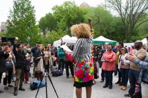 Speaker in foreground; event attendees in background at Poetry Reading at the Union Square Market