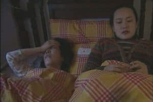 Two women laying in bed, a scene from the Guggenheim Film Festival