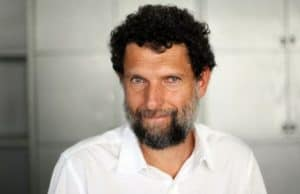 Osman Kavala in a white shirt smiling