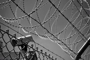 surveillance camera surrounded by barbed wire