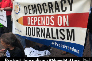 "protestor holding sign that reads ""Democracy Depends on Journalism"""