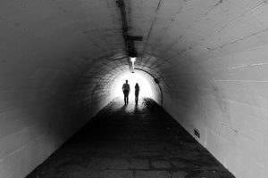 two people walking through a tunnel
