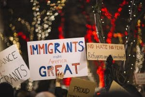 protesters holding signs about immigration