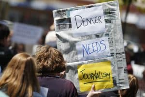 An employee of The Denver Post holds up a sign during a rally against the paper's ownership group, Alden Global Capital, Tuesday, May 8, 2018, outside the paper's office and printing plant in north Denver. (AP Photo/David Zalubowski)