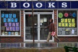 man walks by bookstore with signs