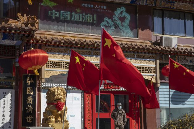 """A worker stands near a Chinese national flag and propaganda which reads """"Go China"""" in Beijing"""