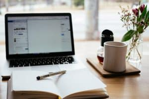 image of a laptop, notebook, and mug