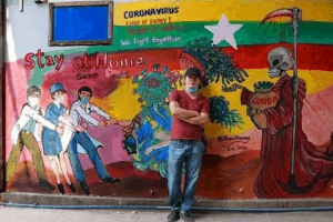 artist standing in front of mural