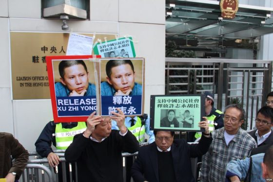 People hold signs in support of Xu Zhiyong's release from prison