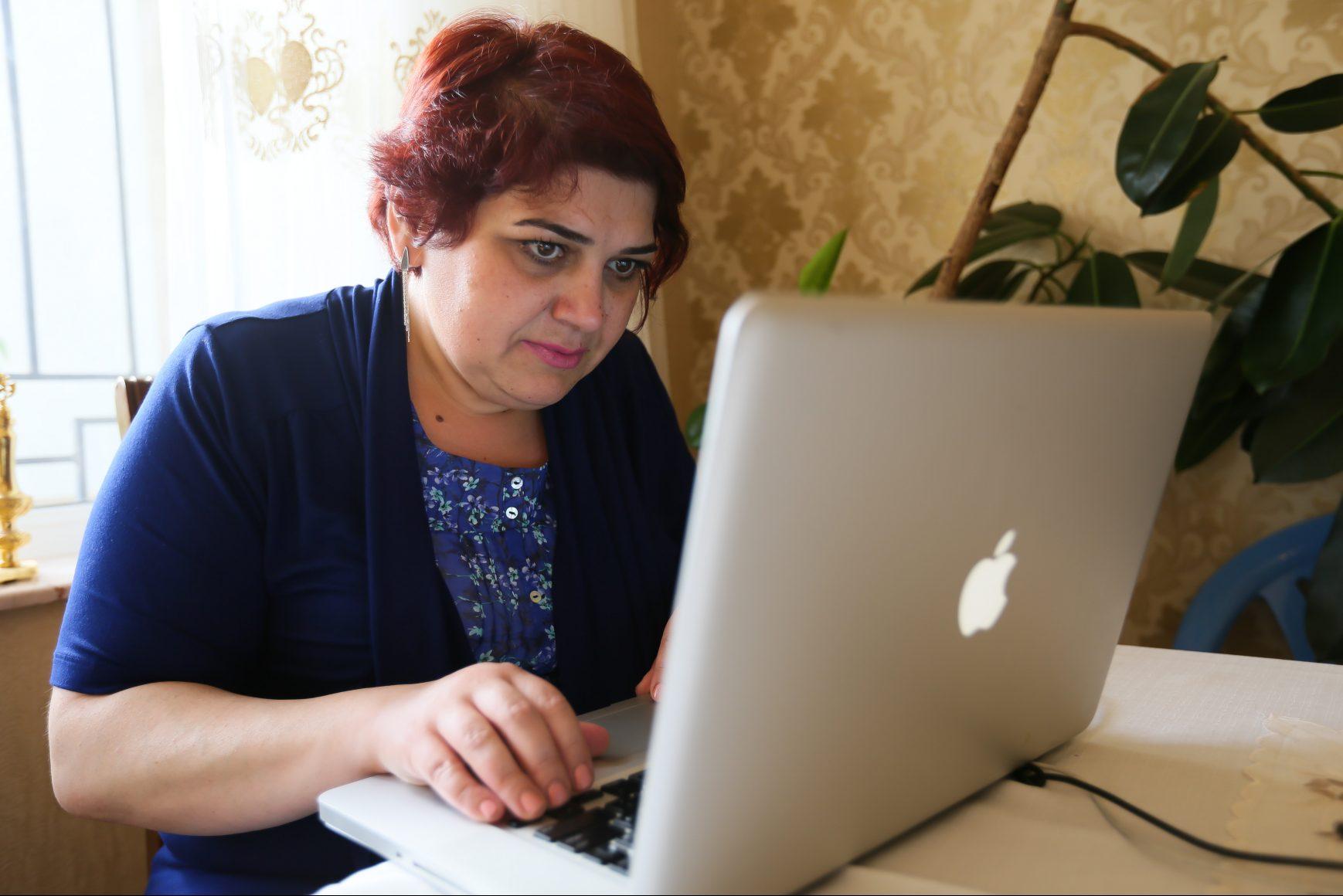 Khadija Ismayilova sits at a computer