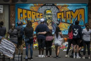 visitors in front of a mural of george floyd