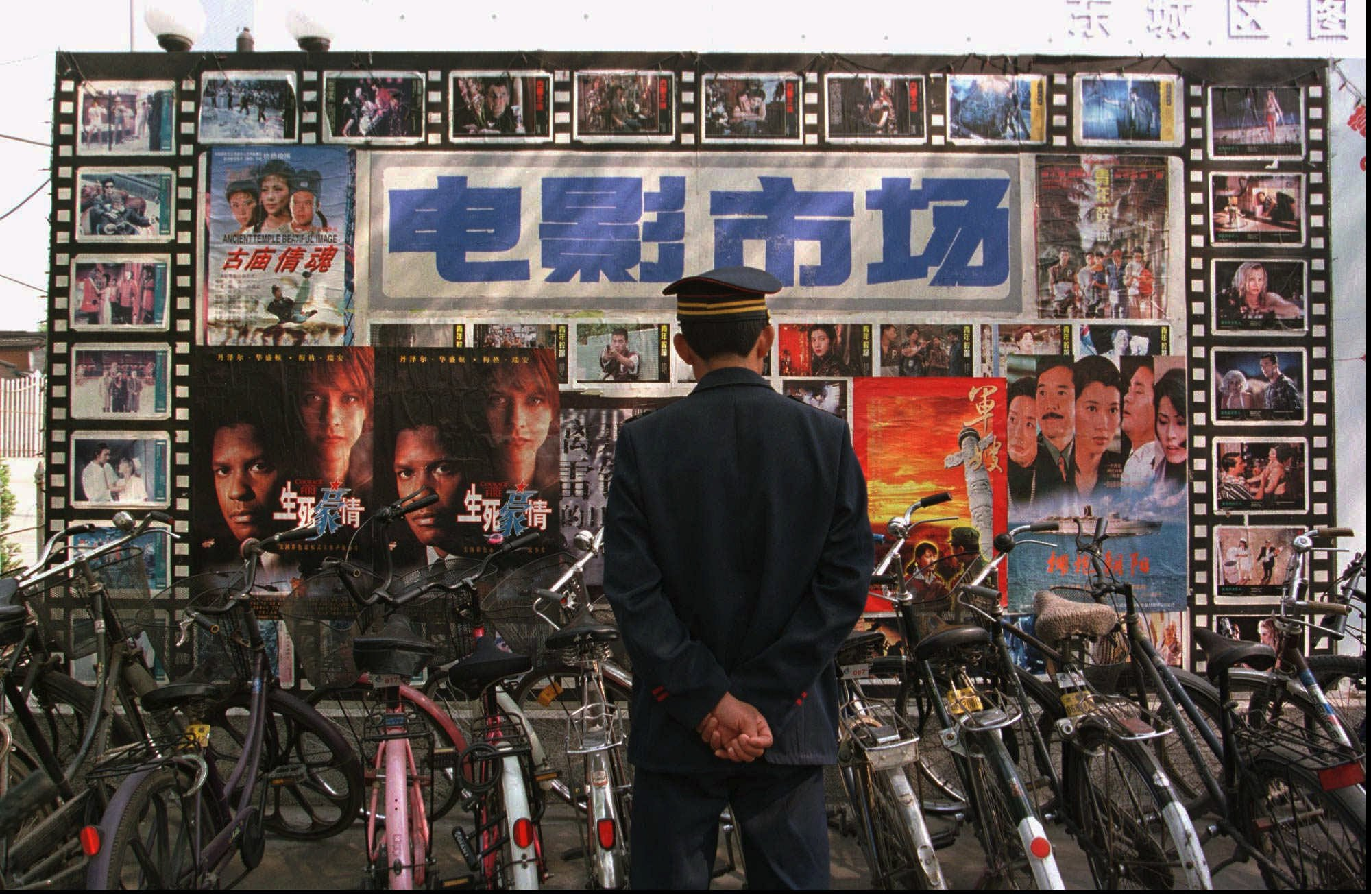 A security guard looks at a billboard full of movie posters outside a Beijing theatre Friday, April 25, 1997. Chinese can now watch a wide selection of movies, ranging from locally produced communist propaganda films to Hollywood blockbusters.