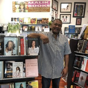 Malik Mohammad, owner of Malik Books, posing next to books on bookshelves