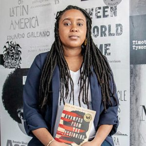 Onikah Asamoa, owner of Fulton Streets Book & Coffee, standing in front of signage and holding Stamped from the Beginning by Ibram X. Kendi