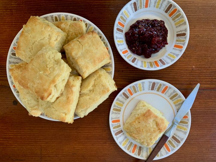 biscuits on a plate next to a plate of jam and one biscuit on a plate