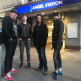 image of four members of belarus free theatre standing in front of a subway station