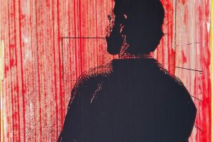 Silhouette of a man facing away from the viewer in a small, empty red room