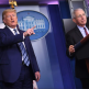 Anthony Fauci at the podium in the White House, standing next to President Trump who is pointing at the audience