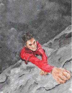 From a bird's eye view, an African American man holds onto the edge of a rocky cliff