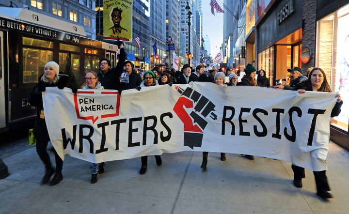Participants hold PEN America's Writers Resist banner, marching in New York City