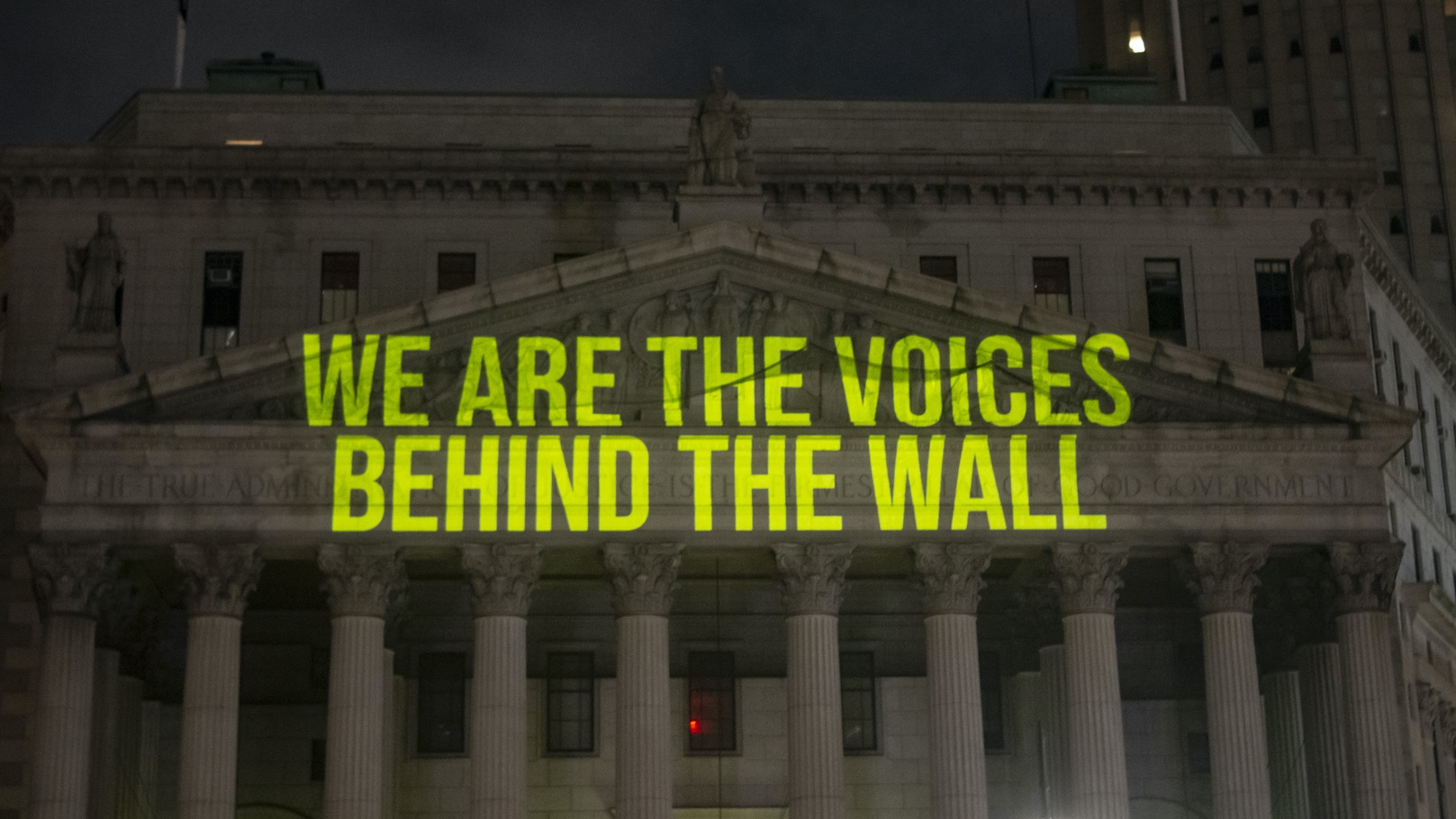 """The words """"we are the voices behind the wall"""" being projected in bright green on the building"""