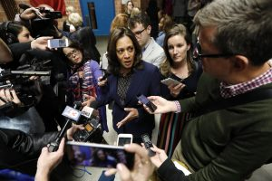 Reporters surrounding Kamala Harris with mics and cell phones