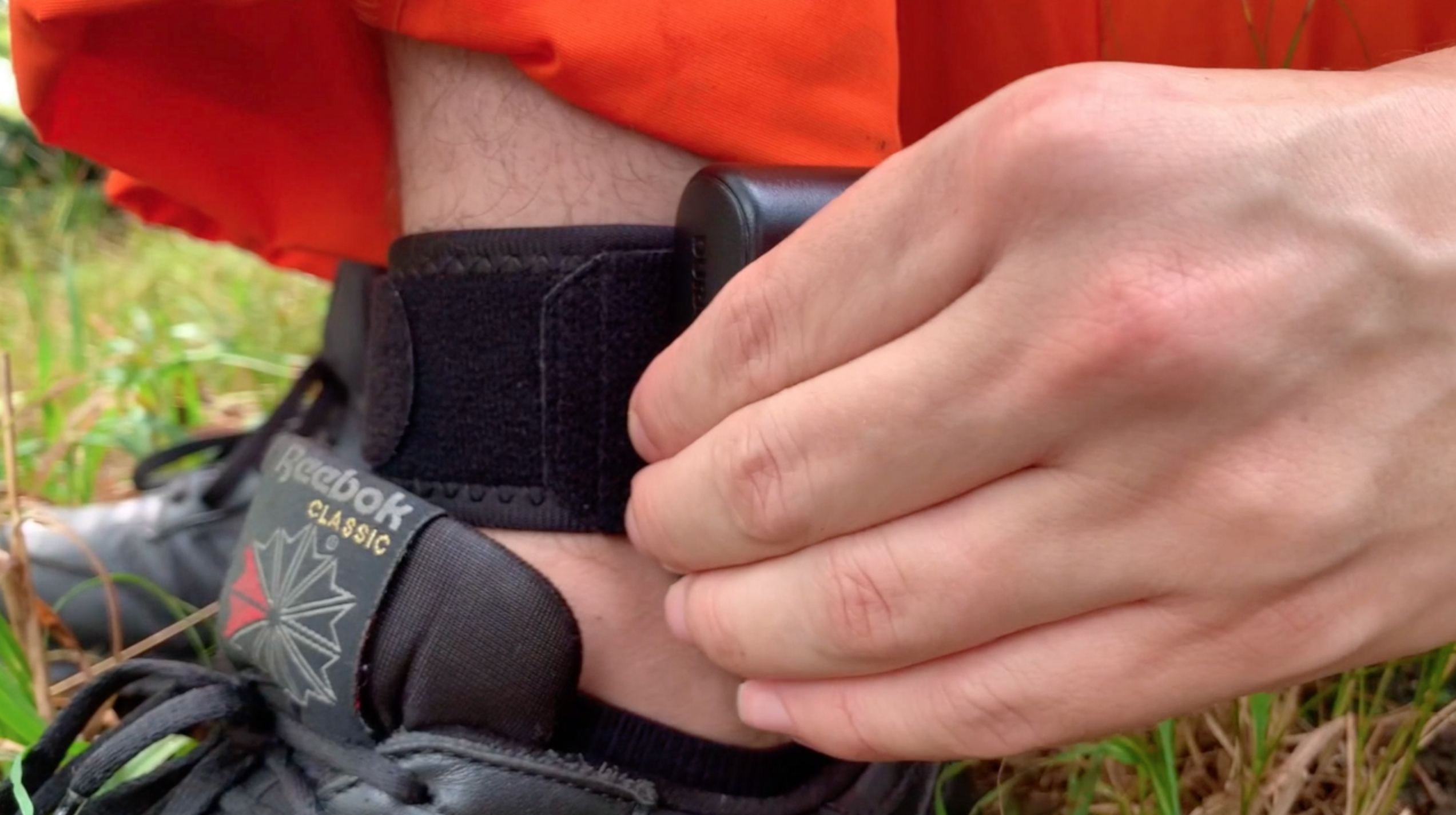 Close up of man in orange jumpsuit pressing a button on his black ankle bracelet