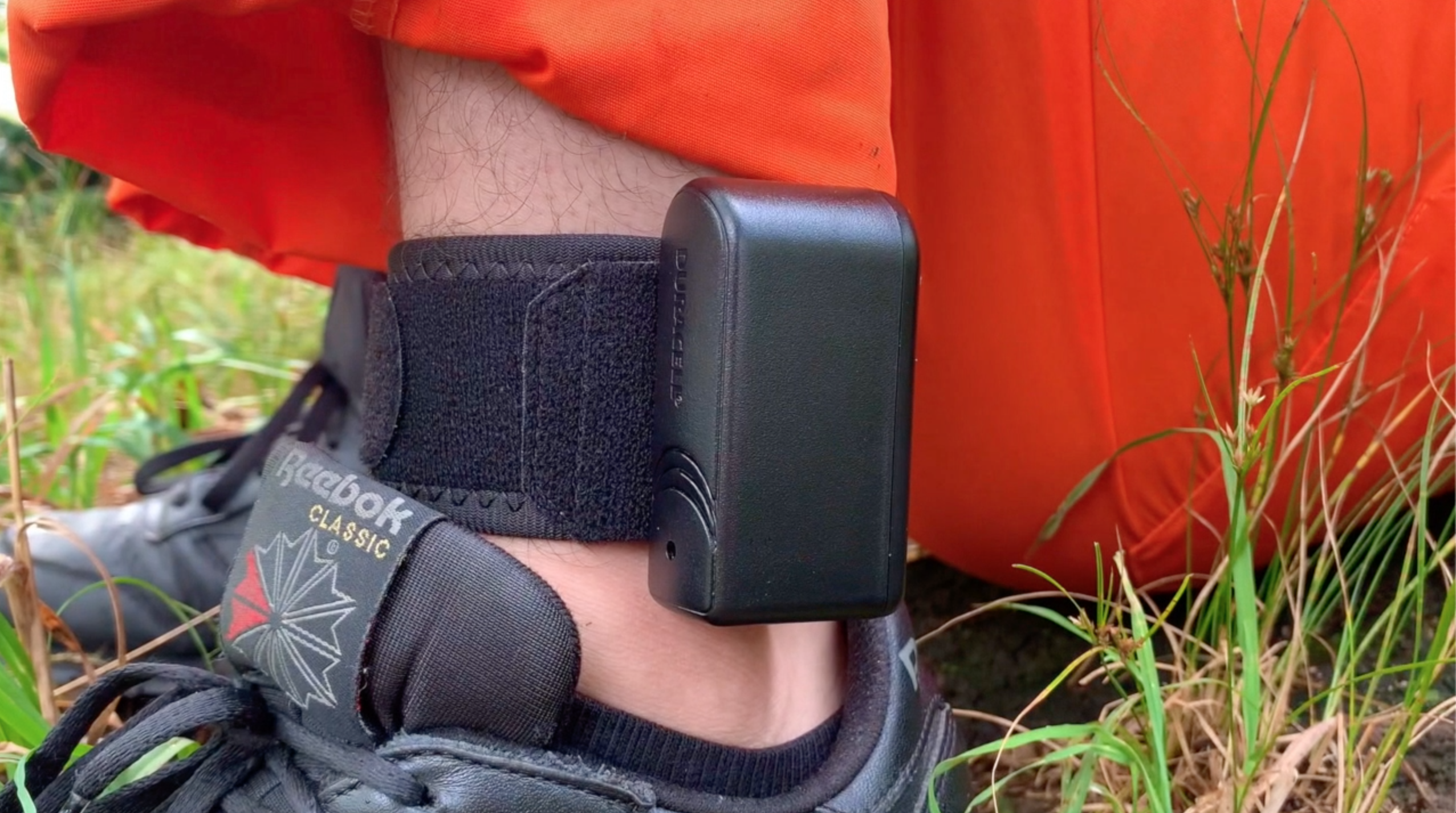 Close up of the black ankle bracelet on the man in the orange jumpsuit