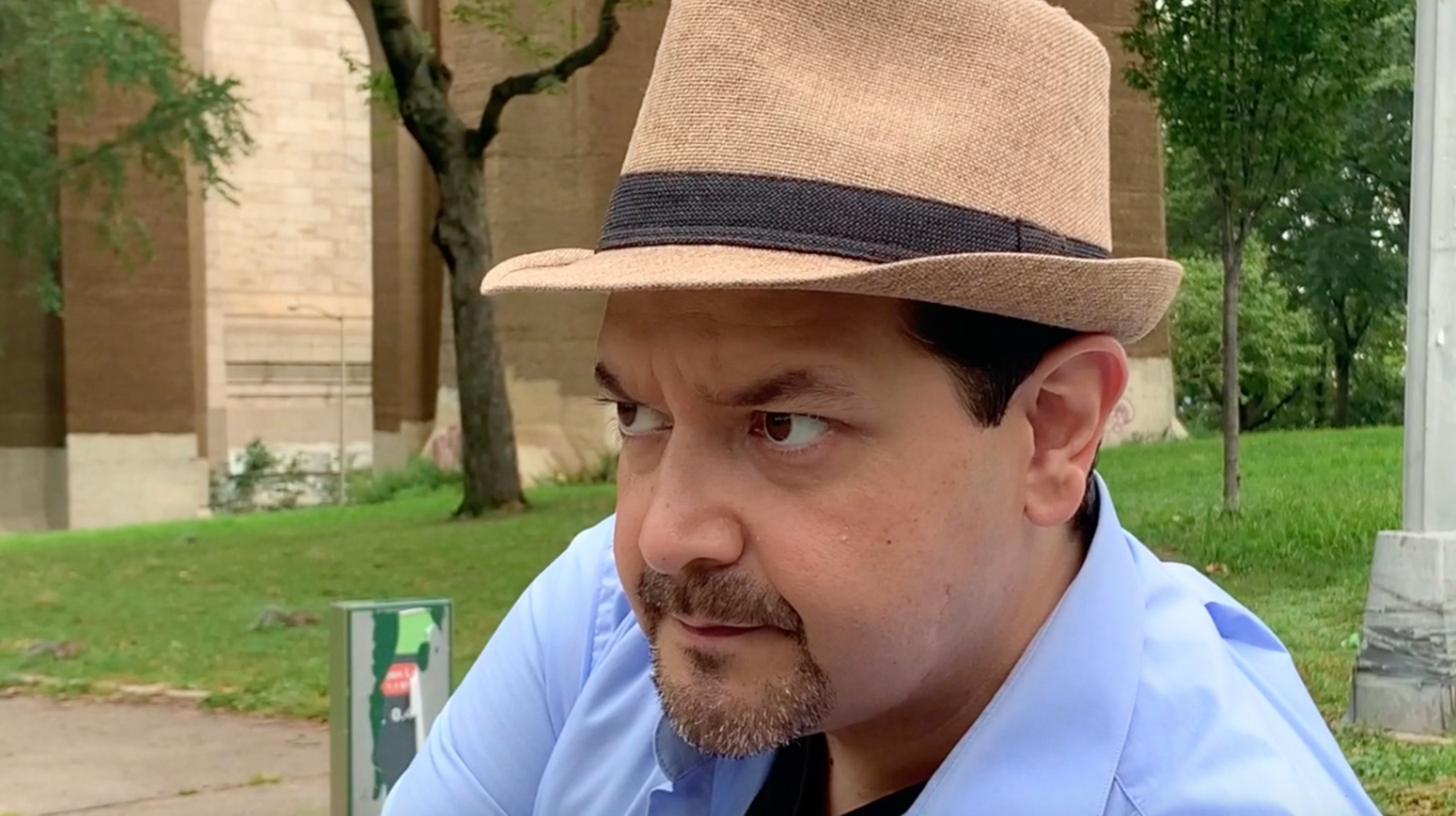 Close up of a man in a brown hat looking curiously into the distance while sitting on a park bench