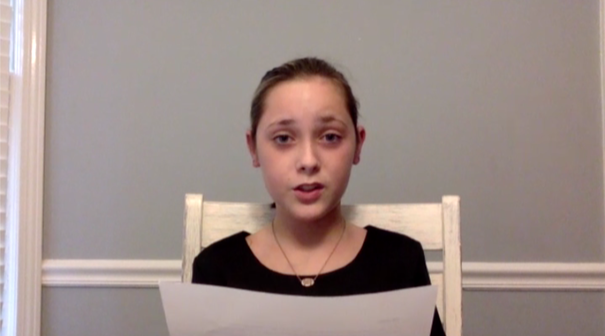 Young child longingly looking into the camera while sitting down and reading from a white piece of paper