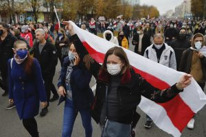 Woman holding a Belarusian flag, marching alongside other protesters