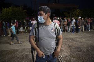 Centered and in front: a migrant at a gas station/food mart in Morales, Guatamela; more migrants in the background
