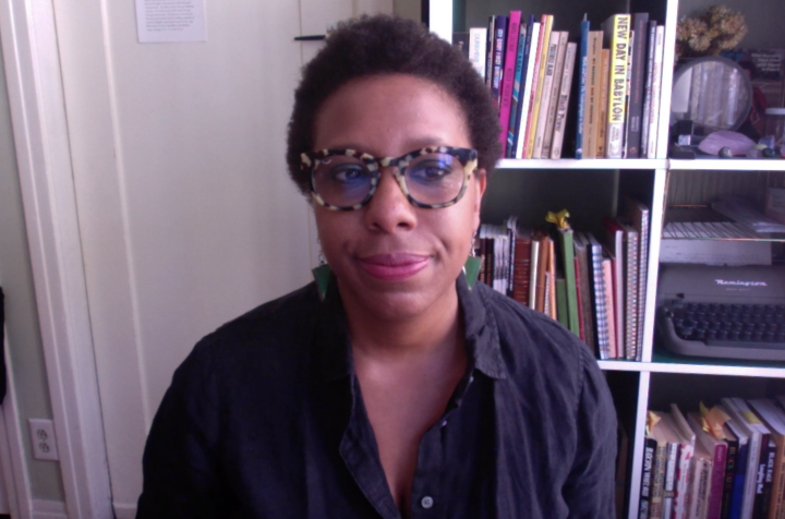 Poet and writer Morgan Parker sitting down in front of a bookshelf