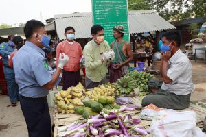 A government official and vendors at a local market in Myttha, Myanmar