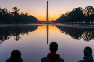 washington monument with three people in foreground