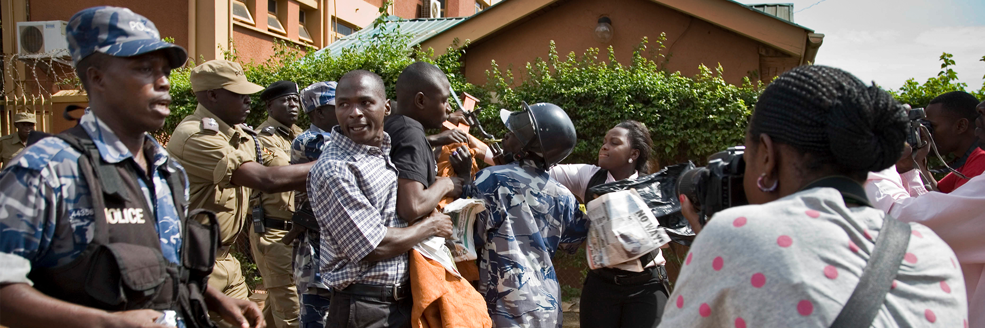 On the left: media and members of Uganda's Human Rights Network for Journalists struggling with police; on the right: person photographing the clashes