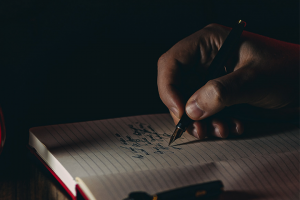 hand holding a pen and writing into a notebook