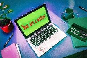 """Potted plant and pen next to a laptop on the left. The laptop screen reads, """"You are a writer."""" in red text on a green background. A PEN America sticker is on the bottom right of the laptop. Next to the laptop, on the right, is a green teacup and a dark green notebook placed on top of a light green folder. The cover of the notebook reads in light pink text, """"A Career & Craft Workshop Series."""""""