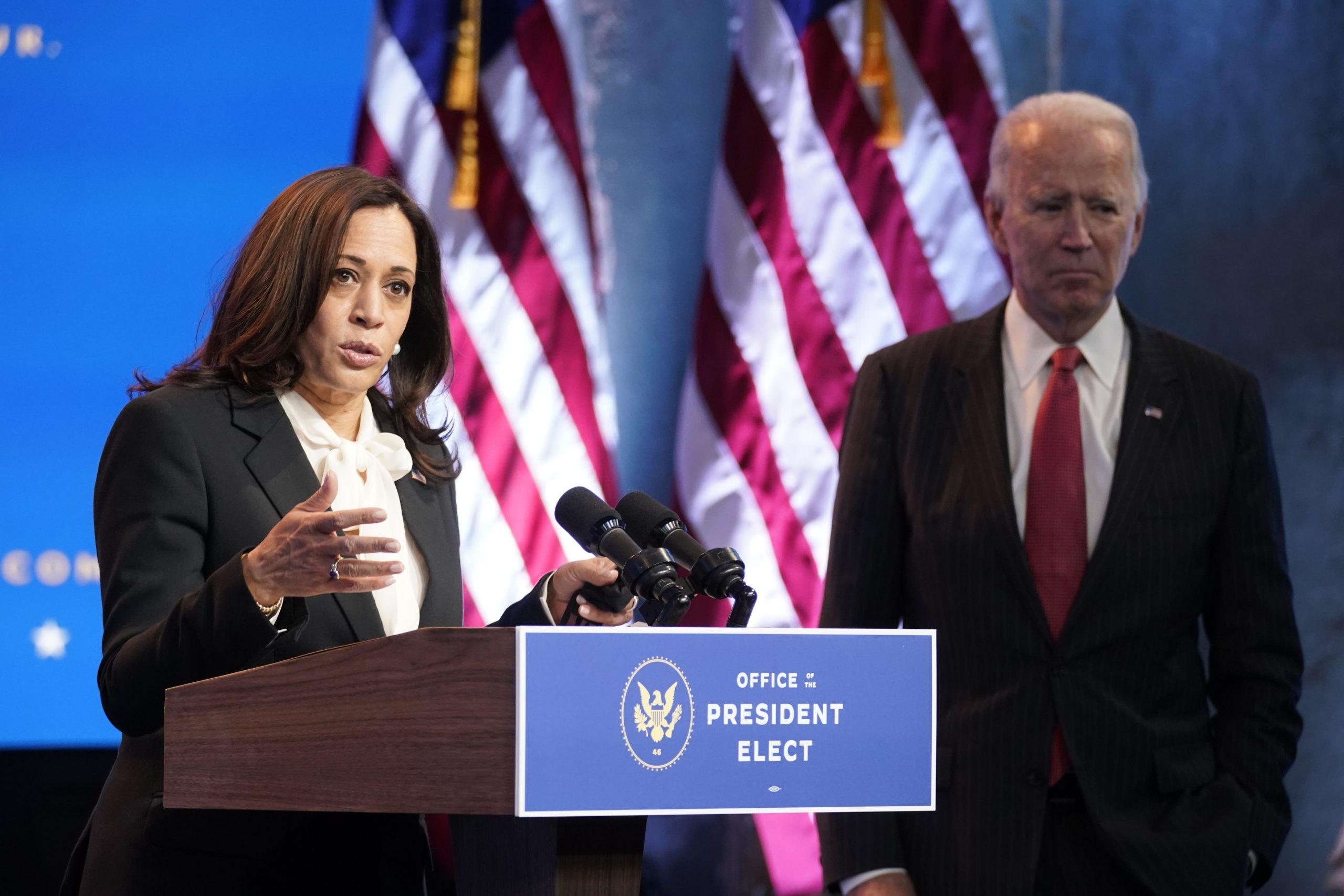Kamala Harris speaking at podium, with Joe Biden in the background