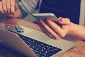 Persona que mira el teléfono celular y la computadora portátil (laptop)