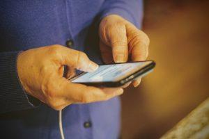 Las manos de una persona mayor sosteniendo un iPhone mientras se está cargando