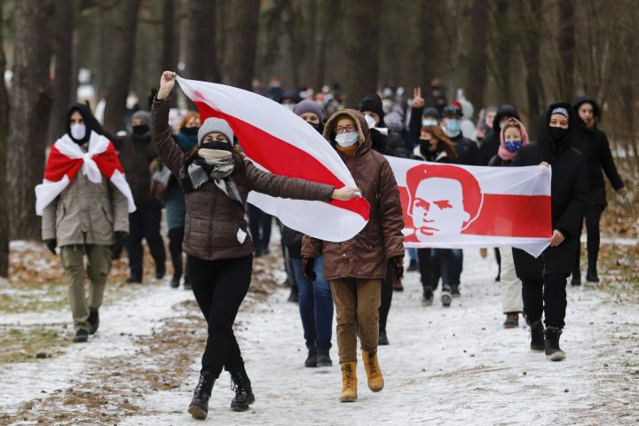 protesters in face masks carrying old Belarusian national flags