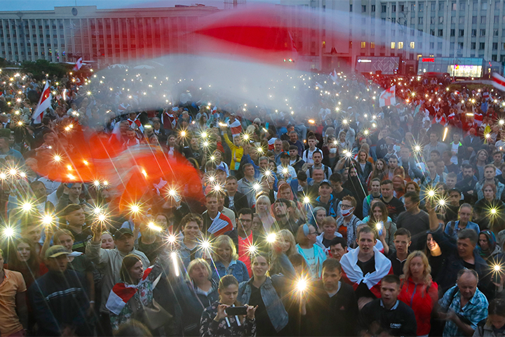 Belarusian protesters holding up their light-up phones, with faded, old Belarusian national flag on top of image