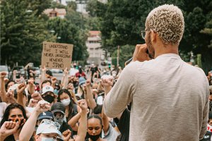 Back shot of an activist speaking in front of a gathered crowd of Black Lives Matter demonstrators