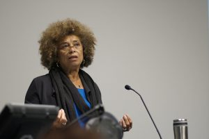 Angela Davis speaks from behind a microphone