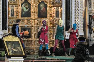 Members of the artistic collective Pussy Riot standing in front of an altar inside a church