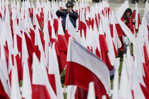a man takes a photograph amid a field of Polish flags