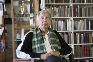 Larry McMurtry seated in front of books