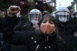 A demonstrator wearing a mask chants and raises her fist in front of a police officer in Istanbul