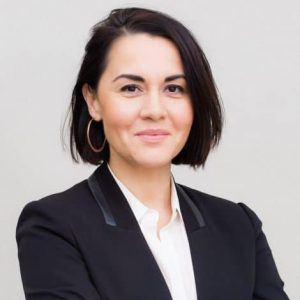 Nora Benavidez headshot (woman with short dark hair wearing a suit against a gray background)